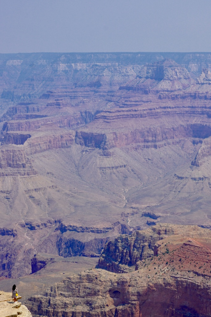 Depicts how small a person is in comparison to the Grand Canyon.